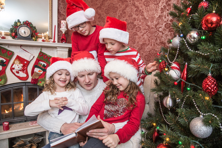 Young dad reads children a book near the fireplace and Christmas tree