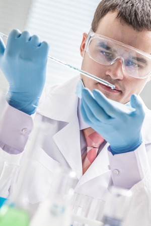 Investigator checking test tubes. Man wears protective goggles Stock Photo