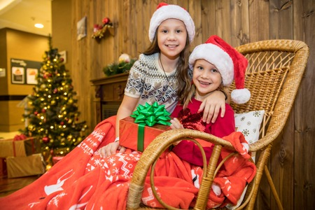 Two little girls in Santa Claus Hat with presents on Christmas party