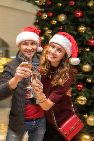 young couple in Santa hat celebrating Christmas with glasses of champagne  under the Christmas tree.