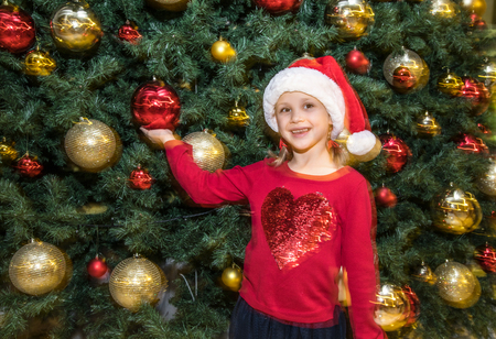 little girl in Santa Claus Hat near christmas tree on Christmas party