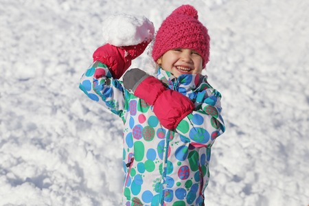 little girl playing  on snow in winter time