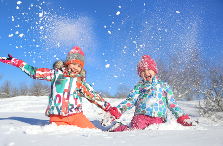 two little girls playing  on snow in winter time Stock Photo