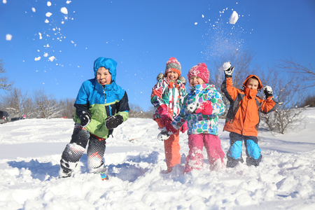 Group of children playing on snow in winter time Stock Photo