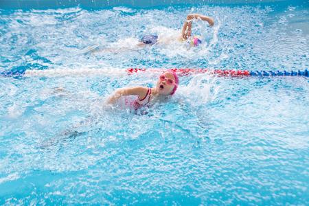 little  girls swimming in blue  pool