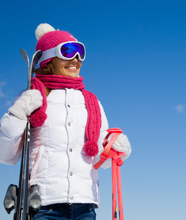 portrait of young smilling woman with ski on winter holiday in winter resort