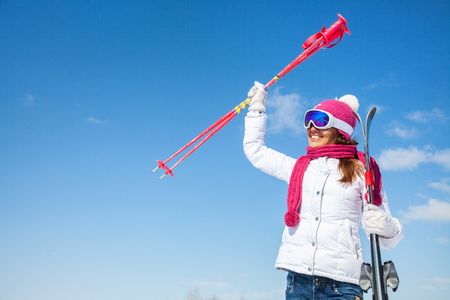 portrait of young smilling woman with ski on winter holiday in mountains