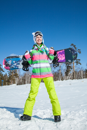 portrait of young smilling woman with snowboard on ski holiday in mountains Banco de Imagens