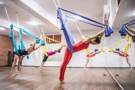 Young women practicing yoga on hammock at health club Banco de Imagens