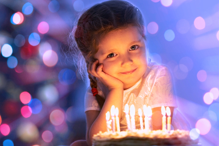 Portrait of cute little girl with birthday cake