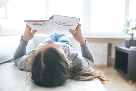 teenager schoolgirl  reads a book at home