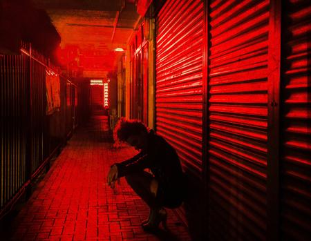 donna triste accovacciata vicino al muro sulla strada delle lanterne rosse di notte