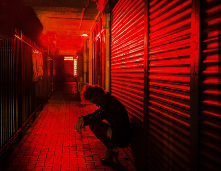 sad woman crouched by the wall on the street of red lanterns at night Banque d'images - 117307760