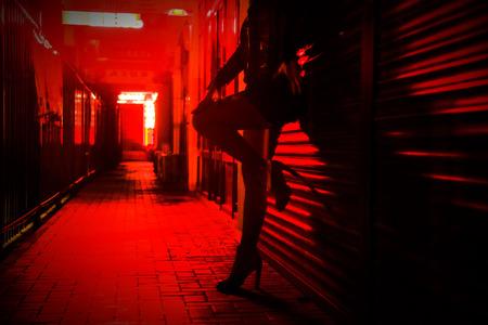 La mujer está de pie junto a la pared en la calle roja de la noche. silueta irreconocible Foto de archivo