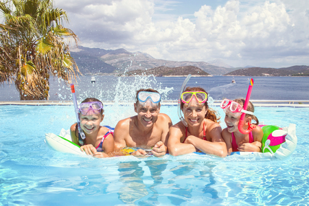 Portrait of big family  swimming in  pool on sea resort Banco de Imagens