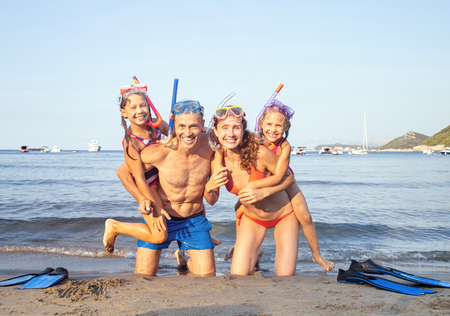 portrait of a happy family having a rest on the beach of a sea resort with fins and masks for diving Banco de Imagens