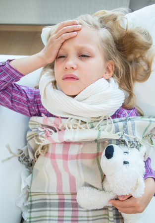 little girl is sick and lies at home on the couch Banco de Imagens
