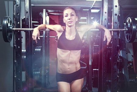 young woman is engaged in bodybuilding at the gym Banco de Imagens
