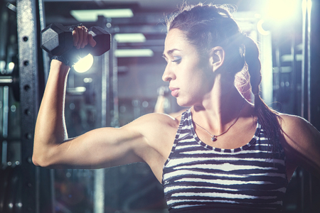 young woman is engaged in bodybuilding at the gym Stock Photo