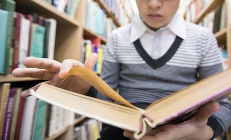 teen boy reading a book in a library Banco de Imagens