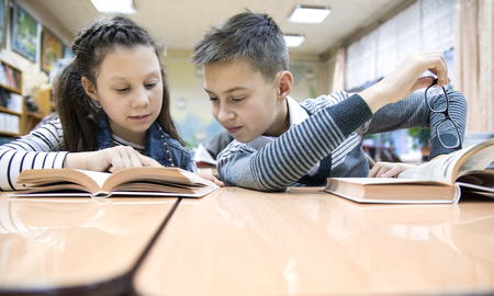 boy and girl reading a book in the library reading room Banco de Imagens