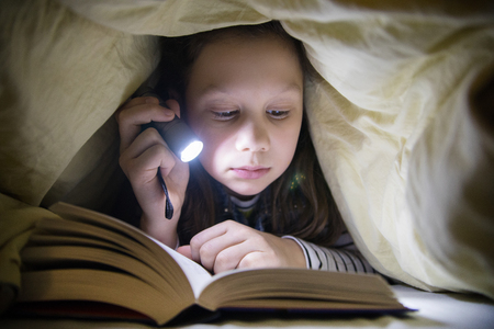 girl reading a book under the covers with a flashlight