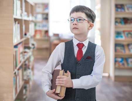 smart boy with books in his hand in the library