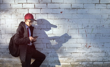 teen boy with a phone in his hand casts a shadow of a reading man