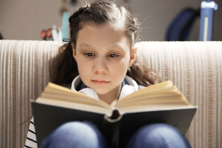 girl reading a book on the couch at home