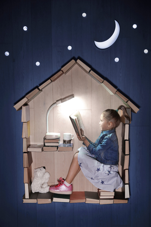 Conceptual photo of a girl reading a book in a house of books. Outside - night, moon and stars
