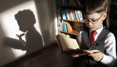 clever boy with a book in his hand casts a shadow of Pushkin A.S.