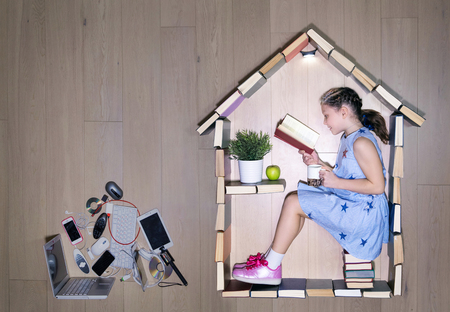 Conceptual photo of a girl reading a book in a house of books. Outside - modern gadgets, digital media