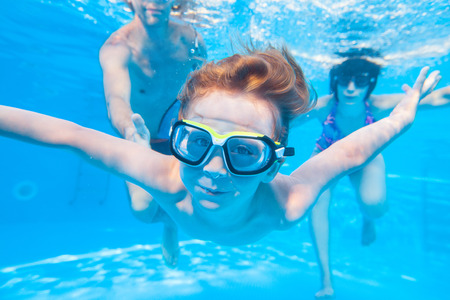 underwater photo of little boy with his family swimming in pool