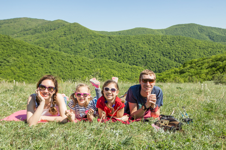 Family with two children resting on a meadow in a hike through mountains Banco de Imagens