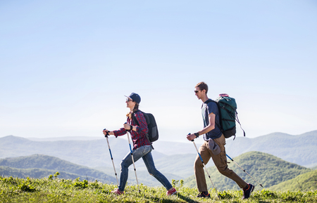young couple, man and  woman, together hiking through the mountains