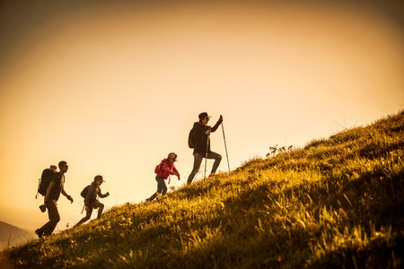 family with two kids have hiking  through the mountains