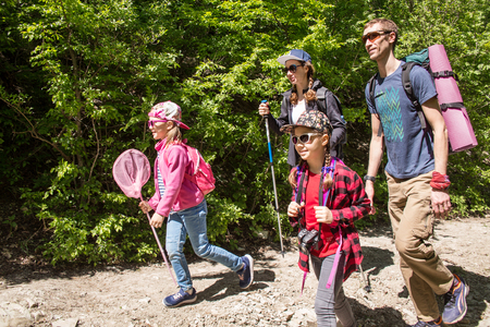 Family with two daughters travels along a beautiful path in the forest Banco de Imagens
