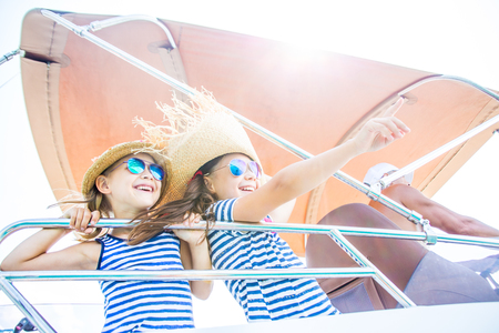 Two little girls enjoying a holiday on a yacht in the sea