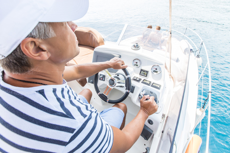 young man is driving a beautiful yacht on the steering bridge in the sea