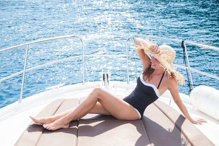 la bella giovane donna si diverte a rilassarsi su uno yacht in mare