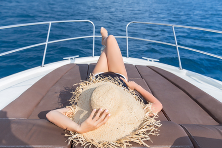 beautiful young woman enjoys relaxing on a yacht at sea