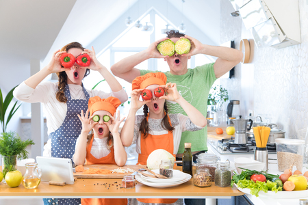 Family with young children have fun cooking together in the kitchen at home