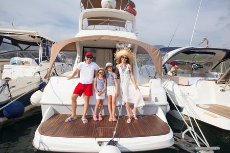 La famiglia felice con bambini si diverte a rilassarsi su uno yacht in mare
