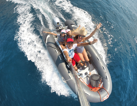 family with children sailing on an inflatable motorboat in the sea Фото со стока