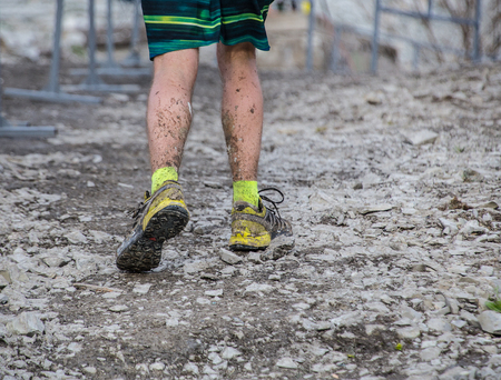 runners feet in sneakers after running in the mud
