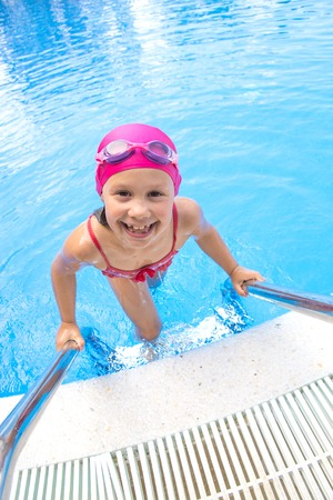 Portrait of little swimmer girl in swimming pool Stock Photo