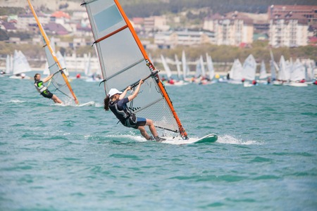 young girl glides on windsurfing in sea Stock Photo