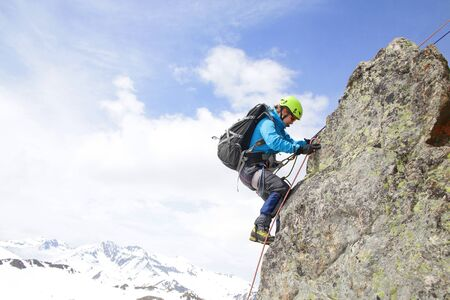 climber woman with ice ax climbs into the mountains against the backdrop of the landscape of snowy mountains