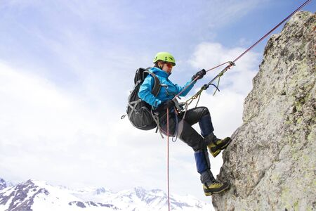 mountaineer woman descends from the mountain in the background of the landscape of snowy mountains