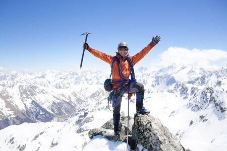 mountaineer with ice ax stands on the top of a mountain in the background of the landscape of snowy mountains